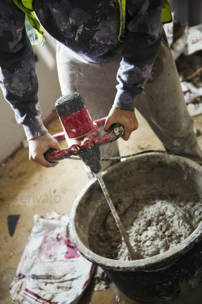 A builder mixing plaster using an electric mixer in a bucket on a construction site.