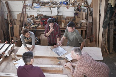 A team of multi-racial factory workers problem solving at a work station in a woodworking factory.