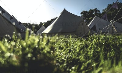 Glamping bell tents, traditional canvas tents in an enclosure on the camping grounds at an outdoor