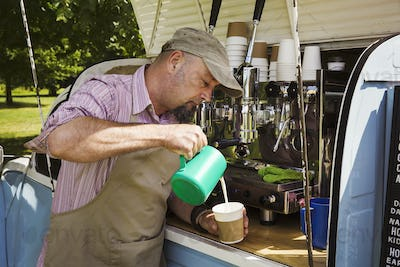 Bearded man wearing apron standing by blue mobile coffee shop, making coffee.