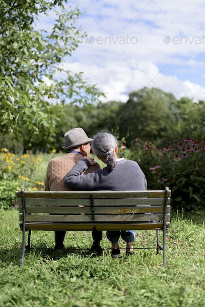 Husband and wife, rear view of elderly man wearing hat and woman sitting side by side on a bench in