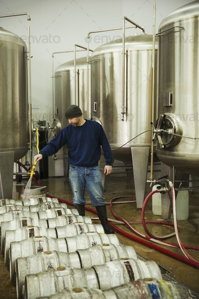Man standing beside the fermentation tanks, cleaning metal beer kegs  with water from a hosepipe.