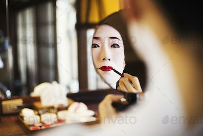 Geisha woman with traditional white face makeup applying bright red lipstick with a brush looking