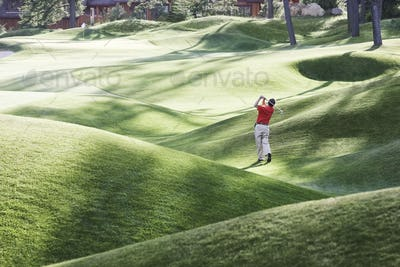 Senior golfer hitting a second shot from the fairway of a golf course.