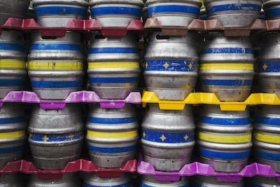 Close up of stacks of metal beer kegs in a brewery.
