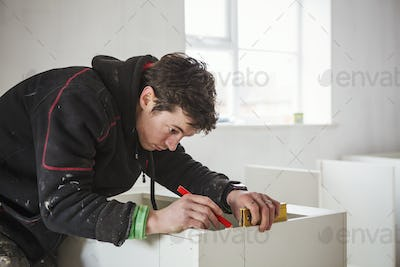 A builder, holding a pencil and ruler, measuring a kitchen unit.