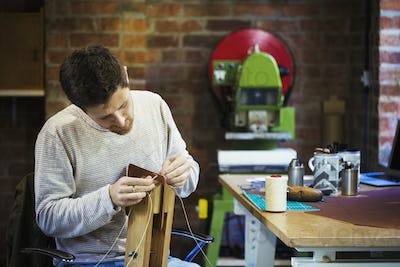 A craftsman in a workshop, threading cord or twine through a small handmade object.