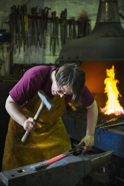 A blacksmith strikes a length of red hot metal on an anvil with a hammer in a workshop.