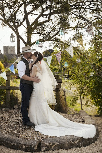 Newlyweds standing outdoors, hugging and kissing.