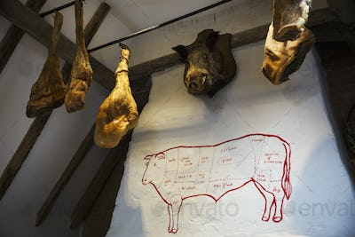 Hams hanging from the ceiling in a butcher's shop, a stuffed boar's head on the wall.