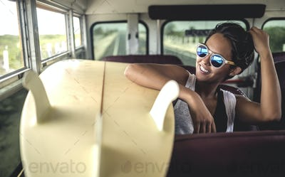 Young woman sitting on a bus with a surfboard.