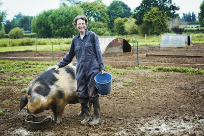 A woman stood by a large pig holding a bucket.