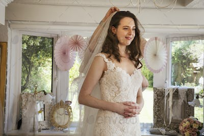 A bride to be, a young woman trying on wedding dresses in a  specialist bridal boutique.