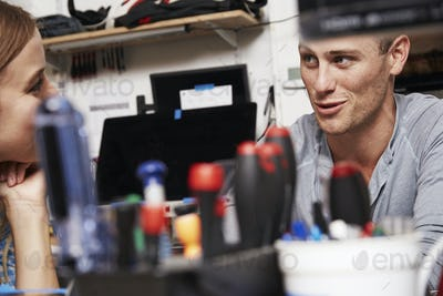 A young woman and man taling to each other in a technology lab or repair shop, with tools on the