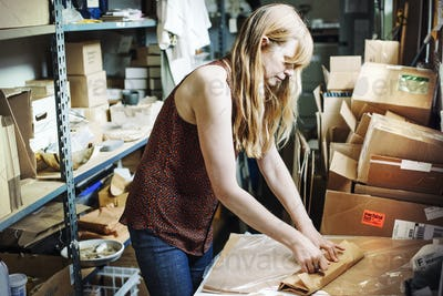 Woman with long blond hair standing in the store room of a shop, wrapping merchandise in brown