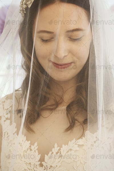A young woman, a bride in a wedding dress with lace bodice, and a net veil over her face.