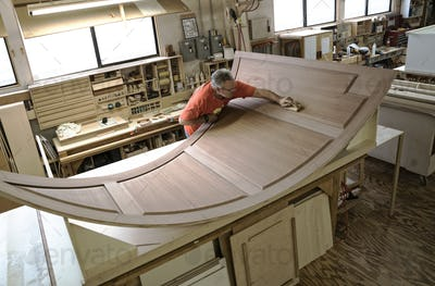 Caucasian carpenter working on curved cabinet face in a large woodworking shop.