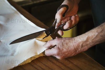 Close up of a man in a sailmaker's workshop cutting a piece of sailcloth with a pair of scissors.