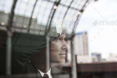 Caucasian businessman staring out a window with reflections.