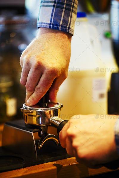 Close up of a barista making a cup of espresso.
