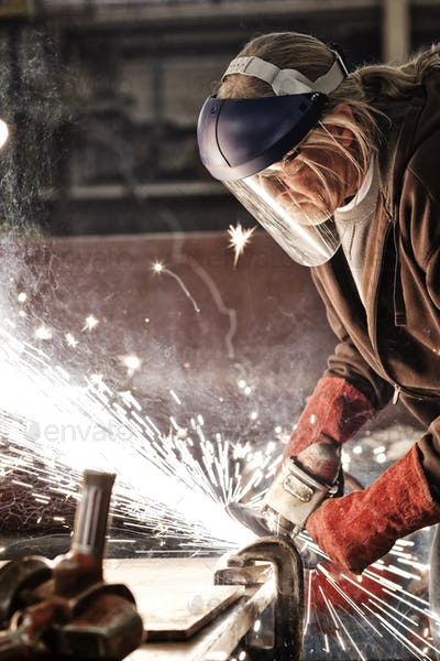 Factory worker grinding a steel edge in a sheet metal factory.