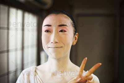 Geisha woman with traditional white face makeup and heavy eyeliner holding up two fingers in a