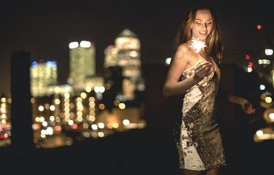 A young woman in a sequined dress dancing on a rooftop at night holding a party sparkler.
