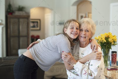 A teenager and a senior woman hugging.