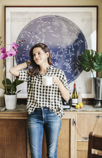 Woman with long brown hair, wearing a chequered shirt and jeans, holding a mug.