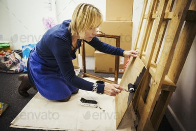 A woman using a roller loaded with black paint on wood.