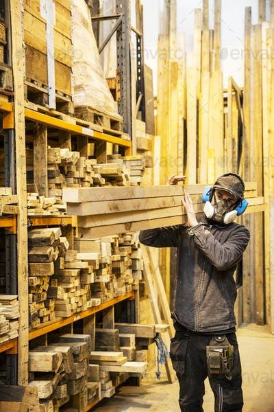 Man wearing ear protectors and dust mask standing in a warehouse, carrying long planks of wood on
