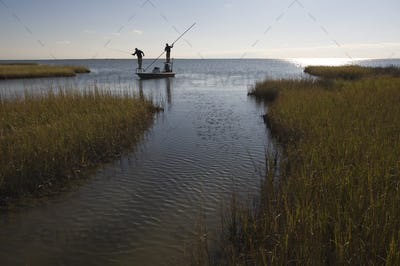 A silhouette of  a fly fisheman and a guide casting for redfish from a flats boat poling skiff in