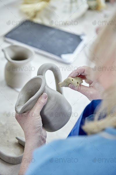 A woman using her hands to shape and smooth a wet clay jug to match another, making a pair.