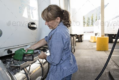 Caucasian woman truck driver filling truck with diesel fuel at a truck stop.