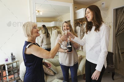A young woman holding a champagne glass and clinking her glass with two women, celebrating the