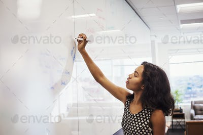 A woman standing in an office writing on a whiteboard.