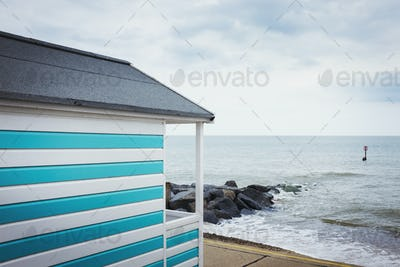 A blue and white striped painted beach hut on a beach on the coast.
