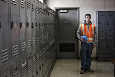 View of a young caucasian factory worker wearing a safety vest and standing next to lockers in a