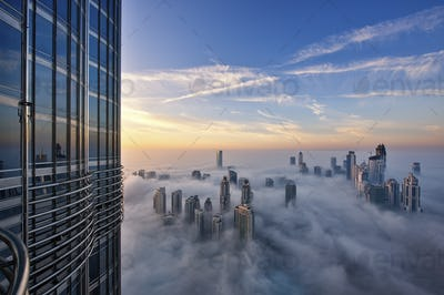 Cityscape with illuminated skyscrapers above the clouds in Dubai, United Arab Emirates.