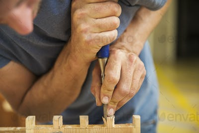 Close up of man working a boat-builder's workshop, joining together two pieces of wood.