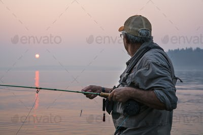 Senior Caucasian male fly fishing for salmon and sea run cutthroat trout in Puget Sound near Port