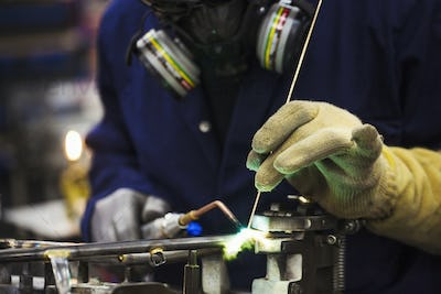 Close up of skilled factory worker welding metal parts of a bicycle in a factory.