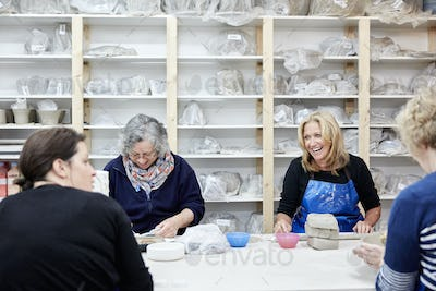 A group of four women chatting together and working on their pots in a pottery studio.