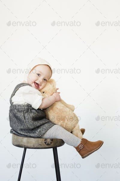 A young child, a girl sitting on a tall stool holding a teddy bear.
