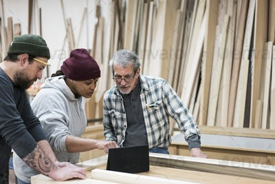 A group of mixed race carpenters discussing a project at a work station in a large woodworking shop.