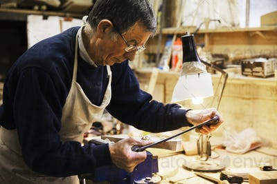 Man standing at a work bench in a carpentry workshop, working on a piece of wood secured in a bench