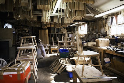 Interior view of a carpentry workshop, wooden chair and furniture parts.