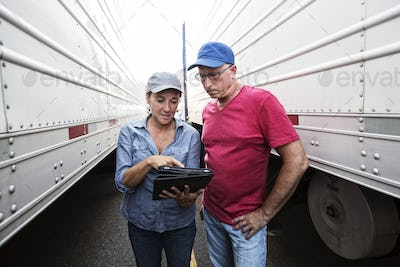 Caucasian man and woman truck driving team going over data on a cell phone while standing between