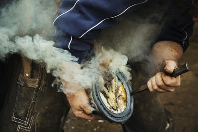 A farrier shoeing a horse, bending down and fitting a new horseshoe to a horse's hoof.  Steam from