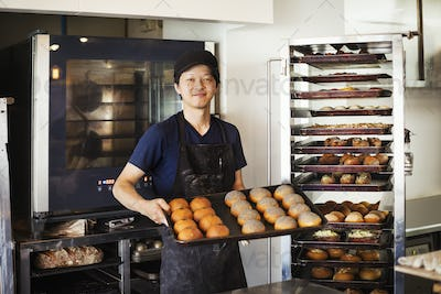 Man working in a bakery, holding large tray with freshly baked rolls, smiling at camera.